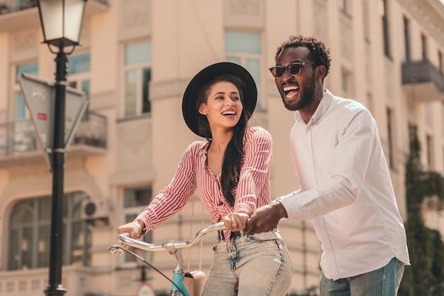 興奮した男性が女性の自転車に乗るのを手伝ってストックフォト