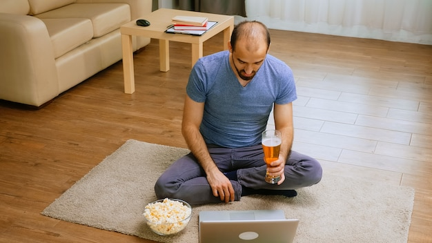 Excited man holding a beer glass during a video call with friend in time of global pandemic.