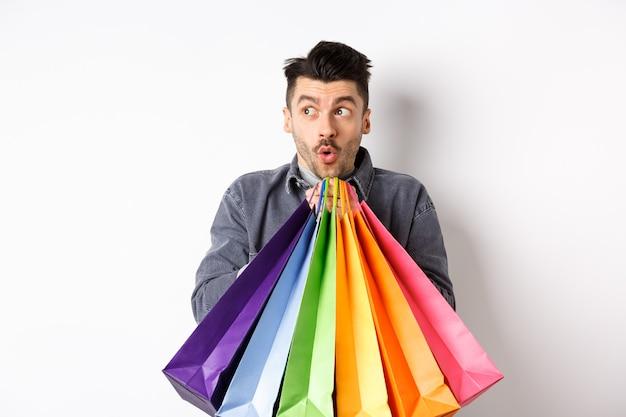 Взволнованный мужчина держит красочные сумки и смотрит влево на специальное промо-предложение в магазине, стоя на белом фоне.