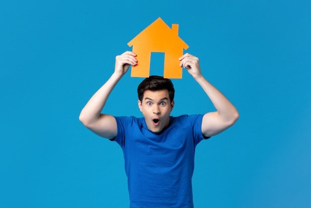 Excited man holding a housing model overhead