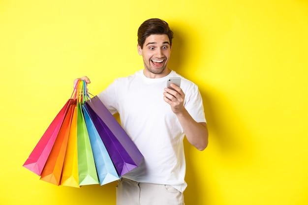 Взволнованный человек, держащий хозяйственные сумки и смотрящий счастливым на экран мобильного телефона, стоящий на желтом фоне.