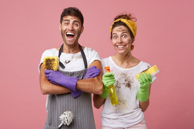 手を繋いでいるカジュアルな服装で興奮している男は、彼の仕事を喜んで汚れたスポンジを持って交差しました。黄色のヘッドバンドと洗剤とスポンジを洗う窓を保持している白いtシャツを着て笑顔の女性