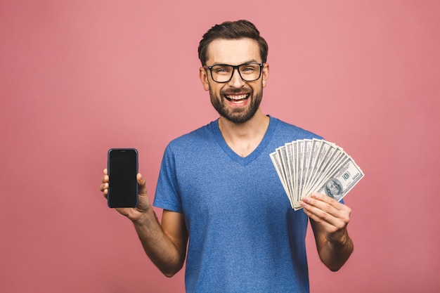 Взволнованный человек в повседневной футболке, держащей много денег в долларовых валютах и сотовом телефоне в руках, изолированных по розовой стене. экран телефона для текста.