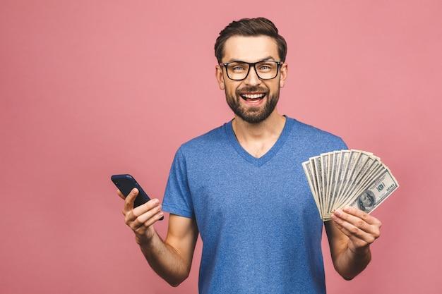 달러 통화와 핑크 벽 위에 절연 손에 휴대 전화에 돈 많이 들고 캐주얼 티셔츠에 흥분된 남자.