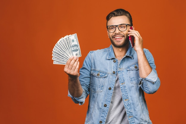 달러 통화로 많은 돈을 들고 오렌지 벽 위에 절연 손에 전화를 사용하는 캐주얼 티셔츠에 흥분된 남자