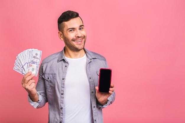 Возбужденный мужчина в повседневной футболке держит в руках много денег в долларовой валюте и сотовый телефон