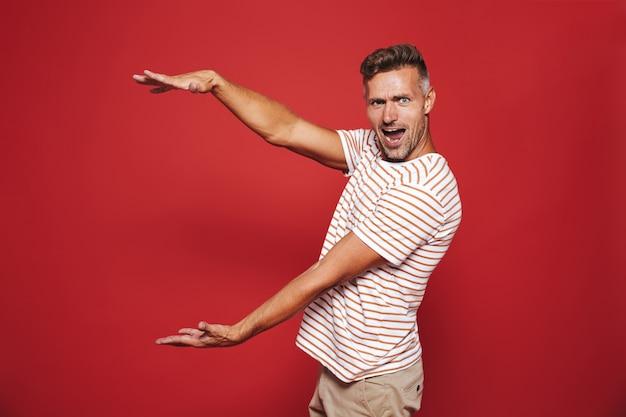 Взволнованный мужчина в полосатой футболке жестикулирует и демонстрирует размер с copyspace, изолированным на красном