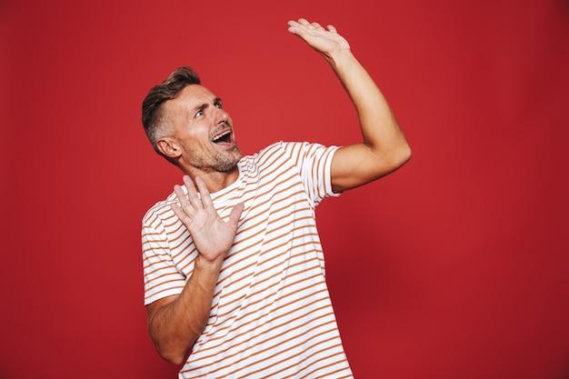 Возбужденный мужчина в полосатой футболке радуется и смотрит в сторону на copyspace, изолированный на красном