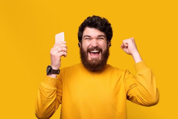 흥분된 남자는 한 손으로 승자 제스처를 만들고 다른 한 손으로 전화를 들고있다.