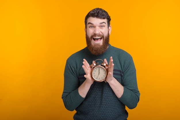 Excited man is showing an alarm clock looking at the camera on yellow background.