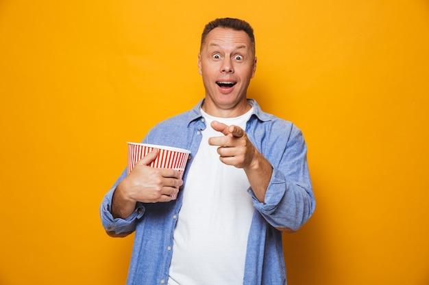 Взволнованный человек, изолированные на желтой стене, ест смотреть фильм смотреть поп-корн