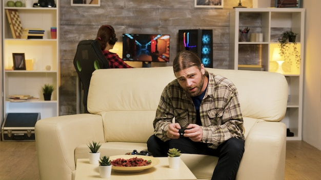 무선 컨트롤러를 사용하여 비디오 게임을 하는 동안 그의 승리 후 공중에서 점프하는 흥분된 남자. 백그라운드에서 컴퓨터에서 편안한 여자 친구입니다.