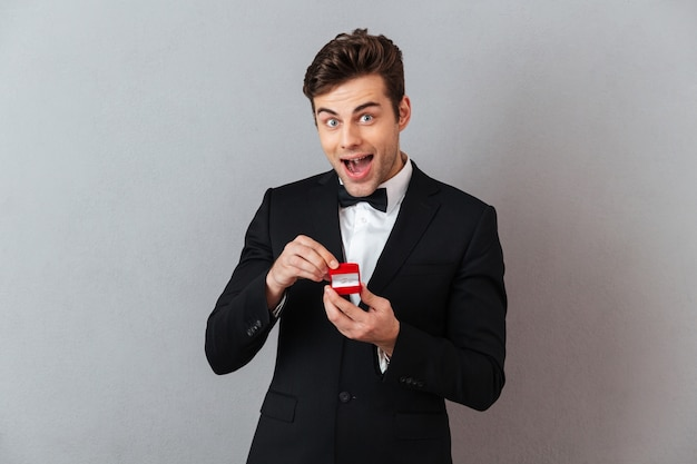 Excited man in official suit holding box with proposal ring.