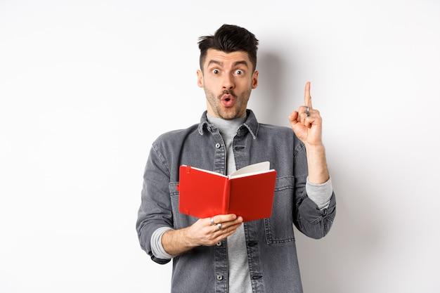 흥분된 남자는 플래너 또는 일기를 읽고, 빨간색 일기를 들고 놀랐고, 유레카 기호에 손가락을 들고 흰색 배경에 서있는 동안 아이디어를 제시합니다.