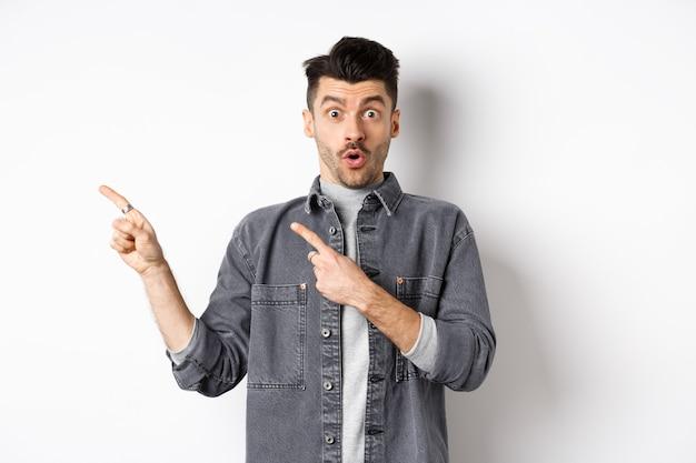 흥분된 남자는 로고에서 왼쪽을 가리키고 불신으로보고 카메라에 와우라고 말하고 멋진 프로모션 할인을 확인하고 흰색 배경에 서 있습니다.