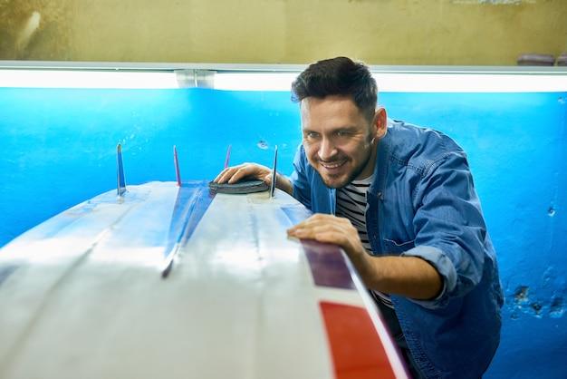 Excited man polishing custom доска для серфинга