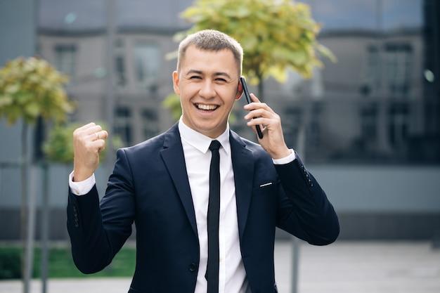 Взволнованный мужчина, читающий хорошие новости на смартфоне на открытом воздухе, удивил мужчину, смотрящего на мобильный телефон на улице