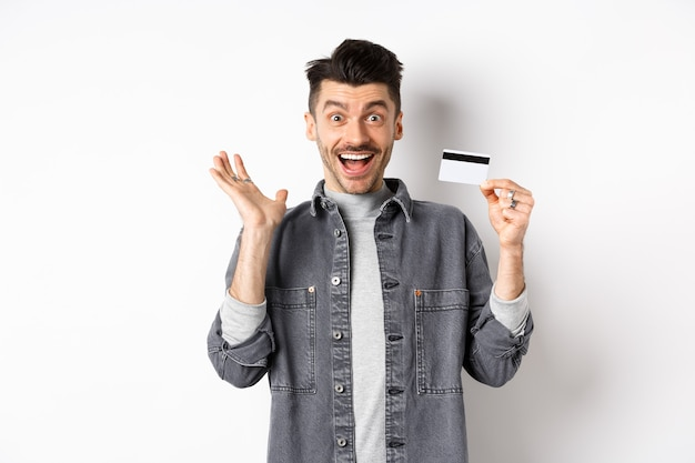 Excited man scream from joy and showing plastic credit card, rejoicing on shopping, standing against white background.
