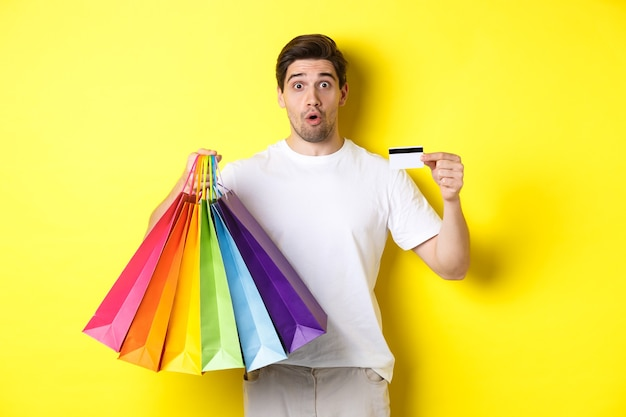 Excited man shopping on black friday, holding paper bags and credit card, standing against yellow background.