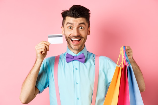 Excited man showing plastic credit card and shopping bags, smiling amazed while buying gifts, standing on pink background.