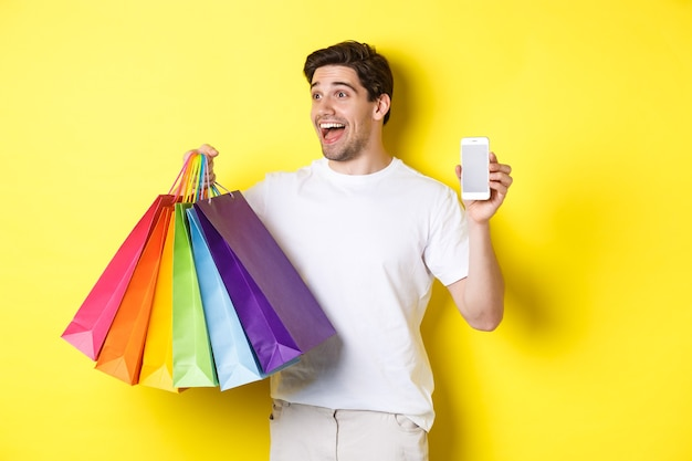Excited man showing smartphone screen and shopping bags, achieve app goal, demonstrating mobile banking application, yellow background