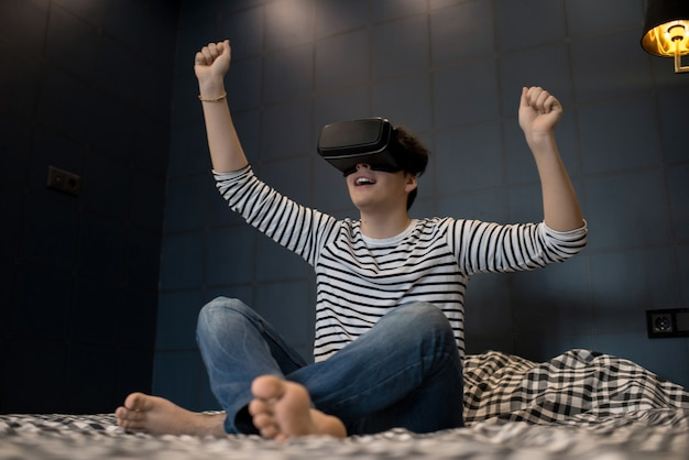 Excited man sitting on bed using vr glasses