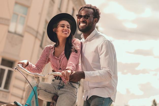 興奮した男は笑顔でガールフレンドが自転車に乗るのを手伝っています