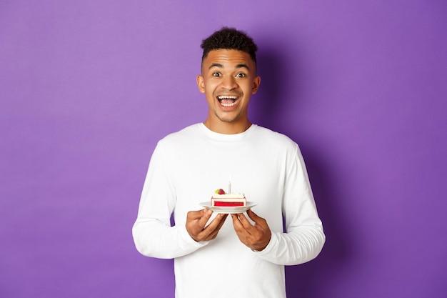 웃 고, 생일 케이크를 들고 소원을 만드는 흥분된 남자