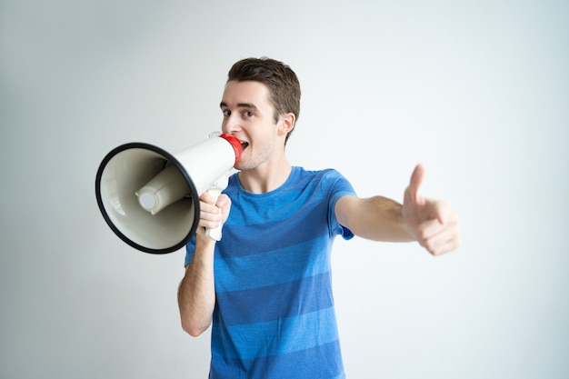 Excited man speaking into megaphone and pointing at you