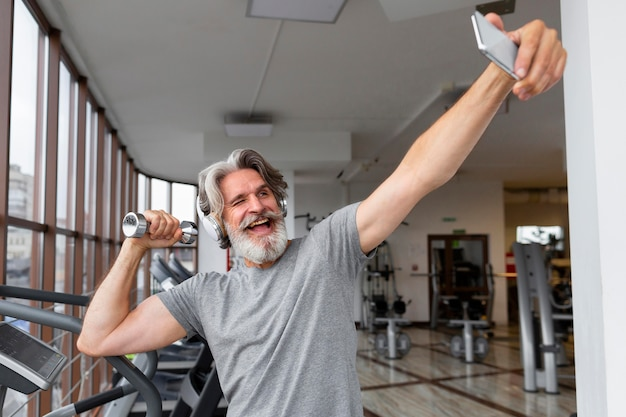 Excited man taking selfies at gym