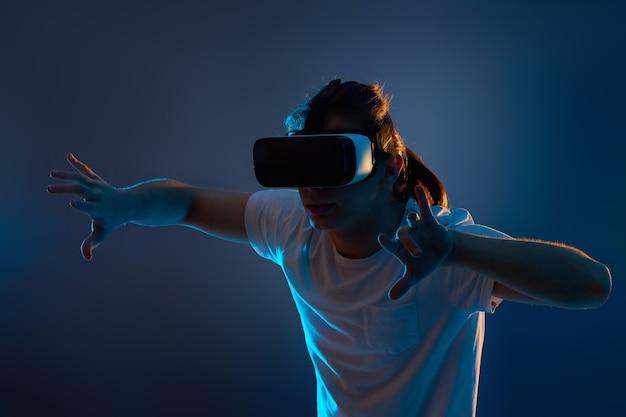 Возбужденный человек, использующий очки виртуальной реальности на синем фоне. неоновый свет.