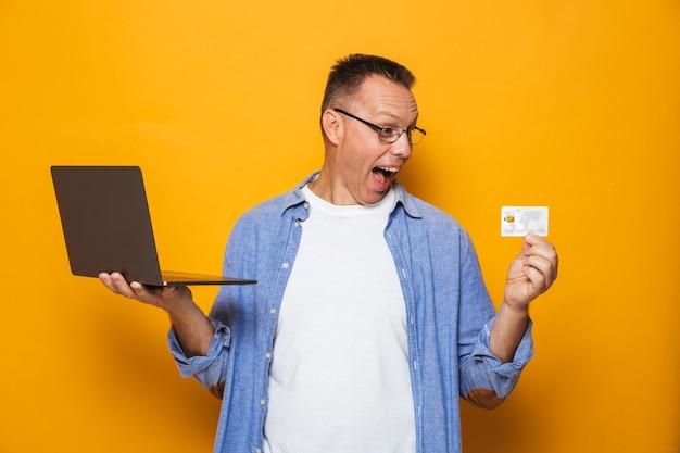 Возбужденный человек, использующий портативный компьютер, держащий кредитную карту.