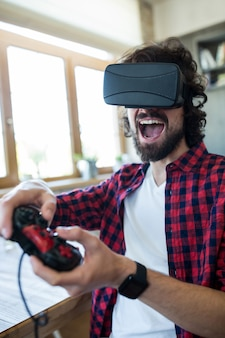 Excited man using virtual reality headset and playing video game