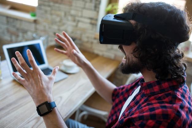 Возбужденный мужчина с помощью виртуальной реальности гарнитуры