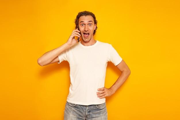 Возбужденный мужчина с телефоном в руке и открытым ртом услышал радостную новость на изолированном желтом фоне