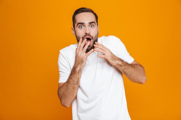 노란색에 고립 된 서있는 동안 수염과 콧수염 코닝 입으로 흥분된 남자