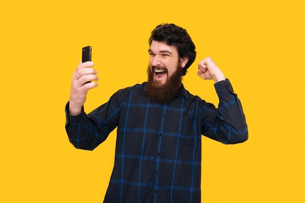 Возбужденный мужчина с бородой, красивый победитель кричит и празднует с поднятой рукой, над желтой стеной