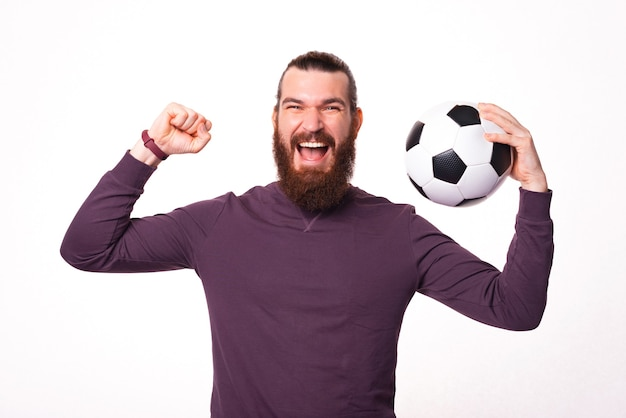 Excited man with beard is screaming with a soccer ball in his hand