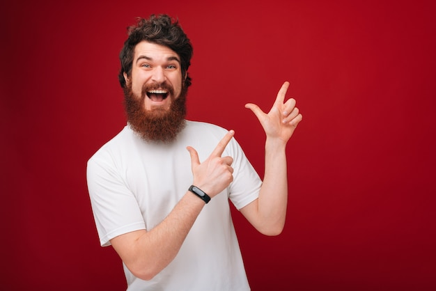 Excited man with beard pointing up  at copyspace while over red wall
