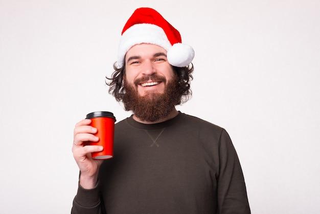 산타 클로스 모자와 스웨터를 입고 커피 한잔 마시는 수염을 가진 흥분된 남자