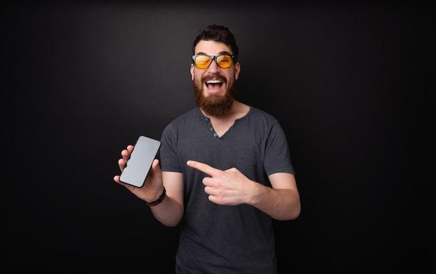 暗い孤立した背景の上に携帯電話を指しているbearddとサングラスを持つ興奮した男