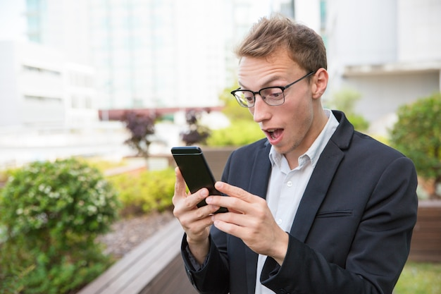 Excited man with cellphone getting shocking news