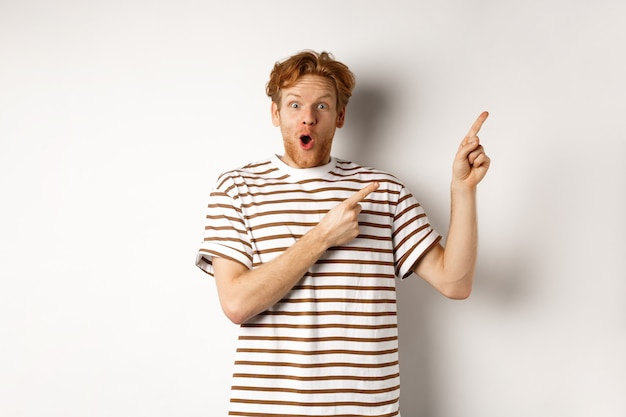 Excited man with curly red hair showing promo offer and looking amazed, pointing fingers at upper right corner logo, white background.