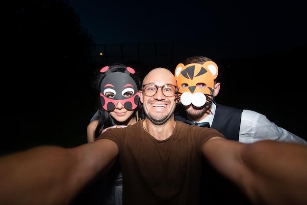 夜selfieを取ってマスクで面白い結婚式のカップルで興奮している男