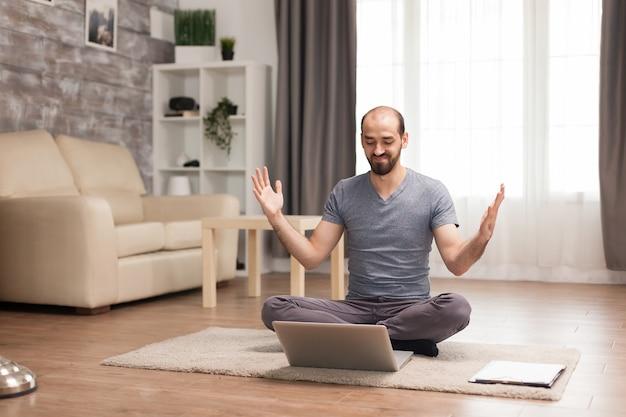 検疫中にコンピューターの前で手を上げて興奮した男。