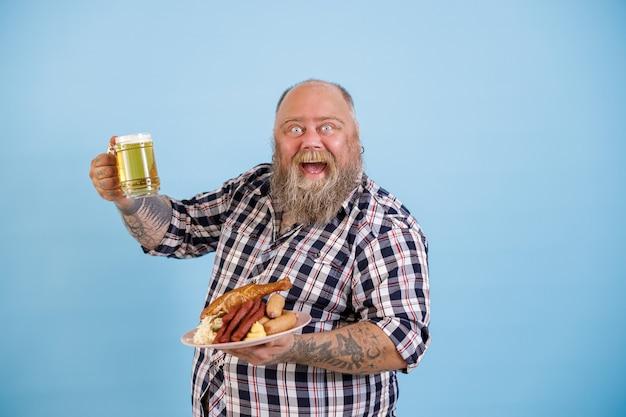太りすぎの興奮した男は、水色の背景においしい料理とビールのグラスを保持します。