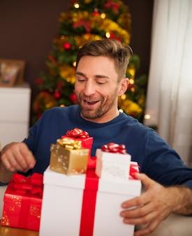 Uomo emozionante con una pila di regali di natale