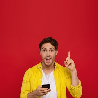 Excited man in yellow shirt using smartphone and showing idea gesture