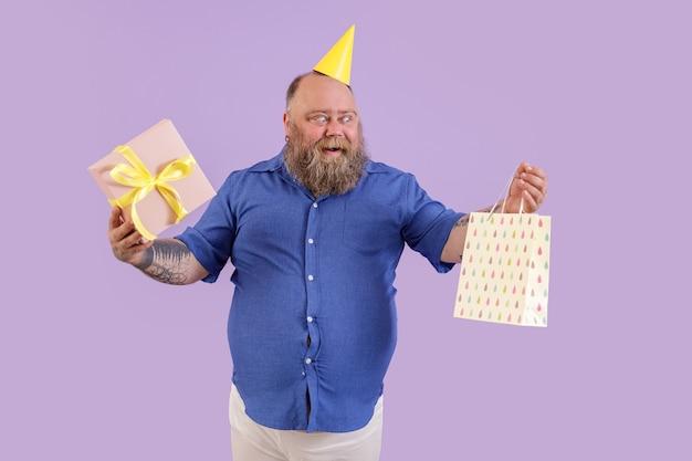 黄色のパーティーハットで興奮した成熟したひげを生やした太った男は、スタジオで紫色の背景に立っているギフトボックスと紙袋を保持します。