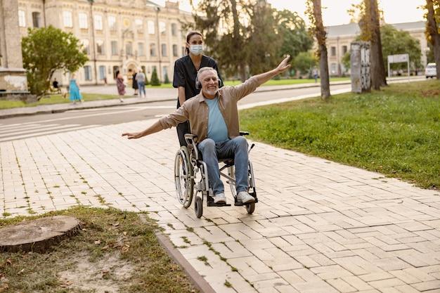 街を散歩中に楽しんでいるヘッドフォンを身に着けている車椅子の興奮した成熟した障害者の男性